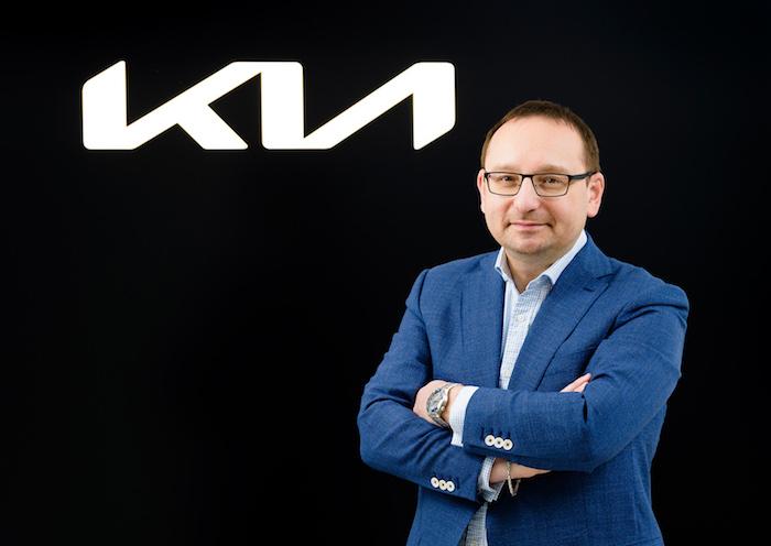Arnošt Barna s novým logem automobilky Kia v pozadí, zdroj: Kia Motors Czech