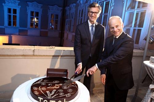 Zprava: Benoit Luc, ředitel divize marketingu a služeb pro Evropu, Total SA, rozkrajuje čokoládový dort připomínající 25. výročí společnosti Total v ČR. V krájení mu zdatně sekunduje francouzský ambasador Jean-Pierre Asvazadourian.